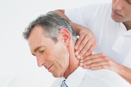 白い背景の上の患者の首をマッサージ男性カイロプラクターのクローズ アップ 写真素材