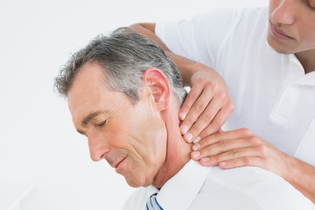 Primer plano de un quiropráctico masculino masaje pacientes cuello sobre fondo blanco Foto de archivo