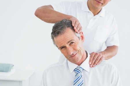 Close-up of a male chiropractor doing neck adjustment in the hospital