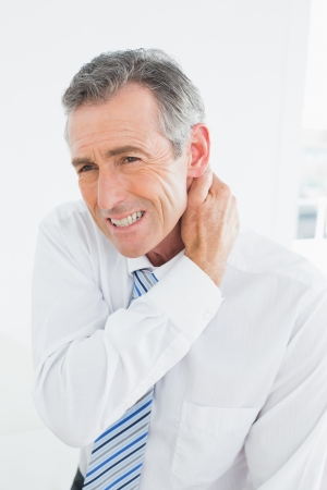 Mature man suffering from neck pain over white background Reklamní fotografie