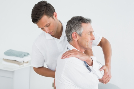 Side view of a male chiropractor examining mature man at office photo