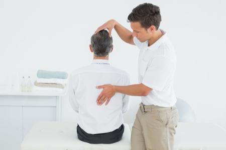 Rückansicht eines männlichen Chiropraktiker untersuchen älterer Mann im Büro