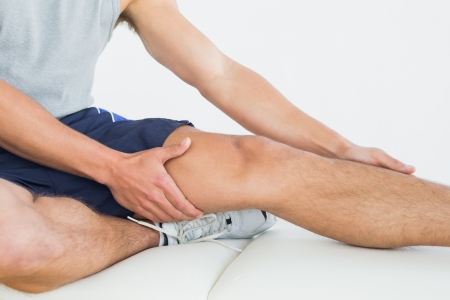 leg pain: Close-up mid section of a man with his hands on a painful leg