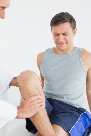 Displeased young man getting his leg examined at the medical office