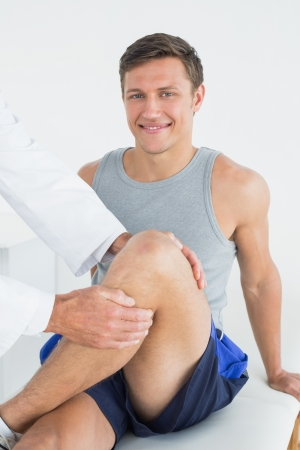 Portrait of a smiling young man getting his leg examined at the medical office