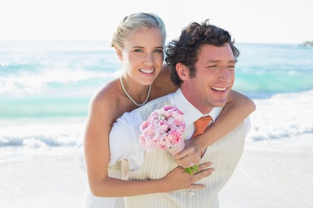 Handsome groom giving his pretty wife a piggy back at the beach photo