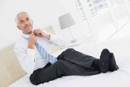 Full length of a smiling mature businessman adjusting neck tie in bed at home