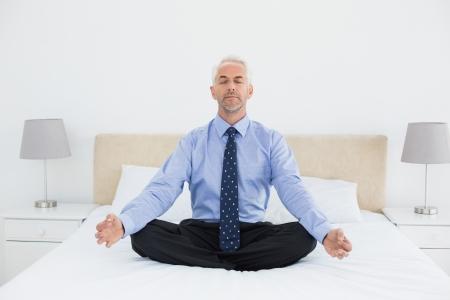 yoga pillows: Full length of a relaxed mature businessman sitting in lotus posture on bed at home