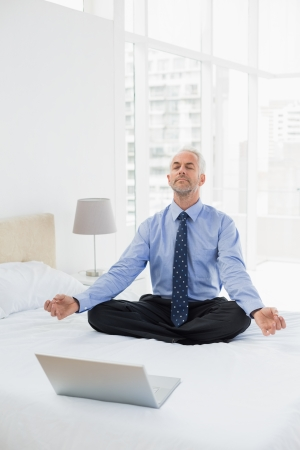 Full length of a mature businessman sitting in lotus pose with laptop on bed at home photo