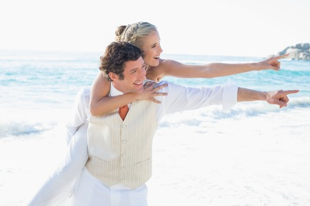 Newlyweds pointing to something and smiling at the beach photo