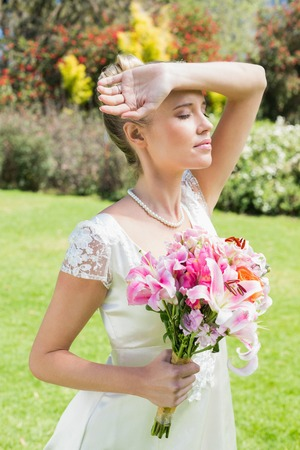holding arm: Beautiful blonde bride holding arm to forehead in the countryside Stock Photo