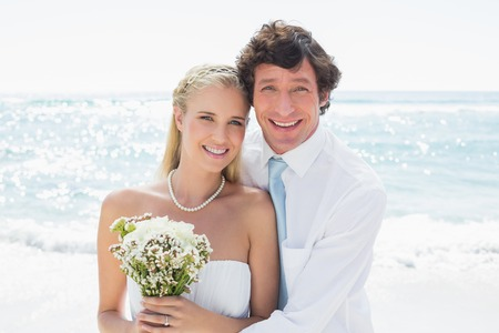 Romantic couple on their wedding day smiling at camera at the beach photo