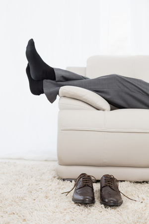 Low section side view of a businessman resting on sofa in the living room at home