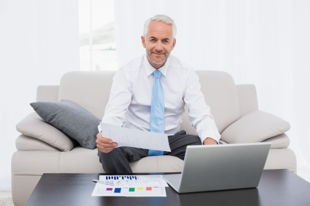 Smiling mature businessman working on graphs and laptop in the living room at home photo
