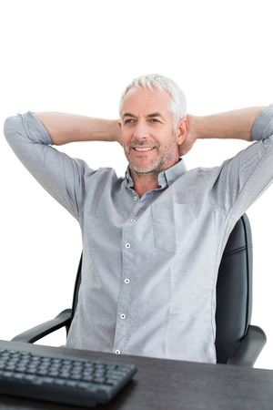 Relaxed mature businessman sitting with hands behind head at desk against white background photo