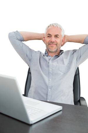 Relaxed mature businessman sitting with hands behind head with laptop against white background photo