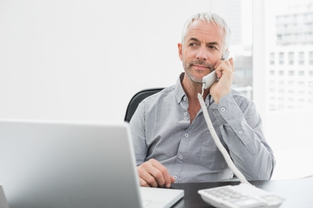 Serious mature businessman on call in front of laptop at desk in a bright office photo