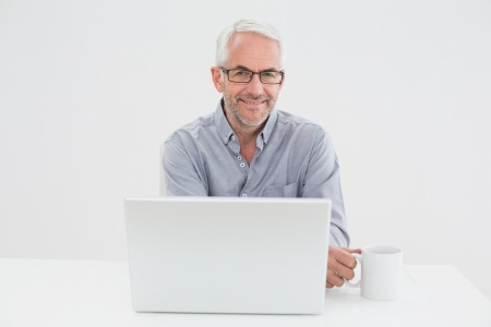 Portrait of a smiling mature businessman with laptop and coffee cup against white background photo