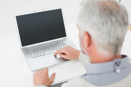grey haired: Close-up rear view of a grey haired man using laptop at desk against white background