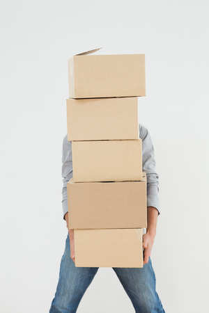 obscured: Obscured man carrying boxes against white background Stock Photo