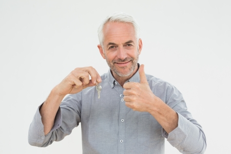 Portrait of a smiling mature man with keys gesturing thumbs up over white background photo