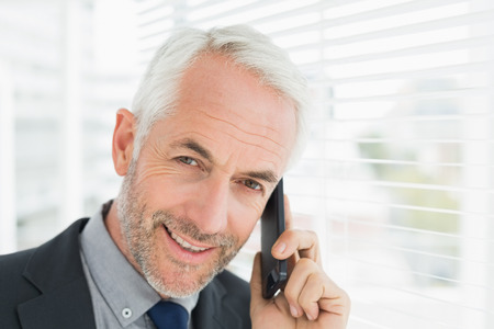 Close-up portrait of a smiling mature businessman using cellphone in office photo