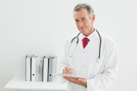 Portrait of a smiling male doctor writing a report at the medical office photo
