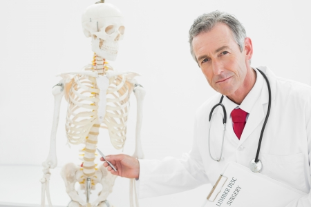 Portrait of a confident male doctor explaining the spine in medical office photo