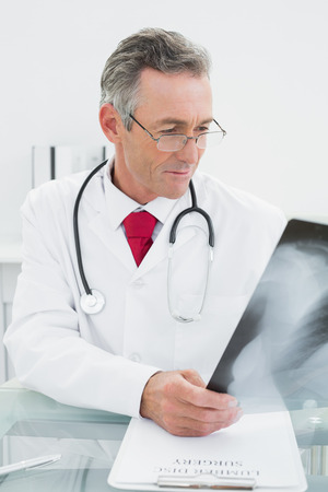 Concentrated male doctor looking at x-ray picture of lungs in the medical office photo