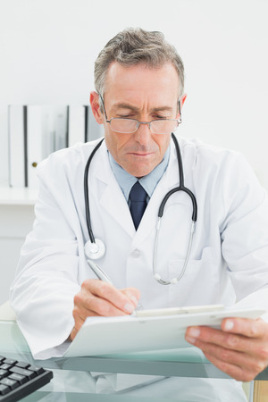 Serious male doctor writing a report at desk in medical office photo