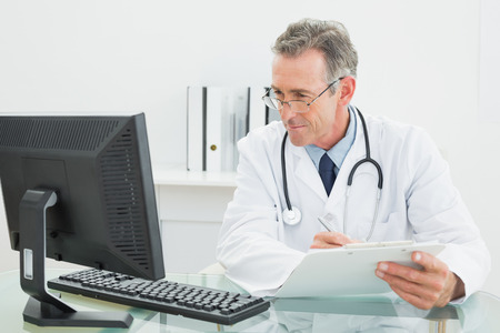 Concentrated male doctor with report looking at computer monitor at desk in medical office