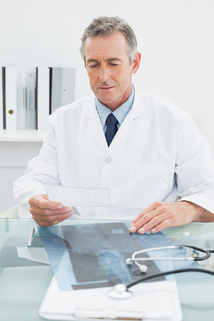 Serious male doctor reading a note at desk in medical office photo