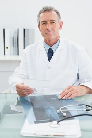 Portrait of a confident male doctor sitting at desk in medical office photo