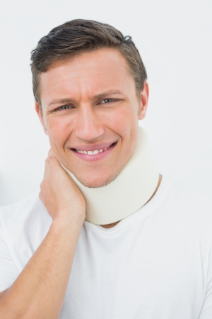 Close-up portrait of a young man wearing cervical collar over white background  photo