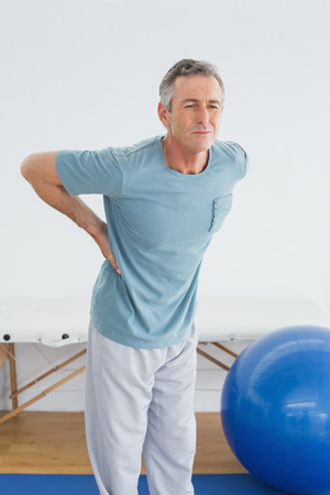 Mature man with lower back pain standing in the gym at hospital photo