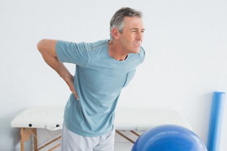 dolor muscular: Hombre maduro con el dolor de espalda de pie en el gimnasio en el hospital Foto de archivo
