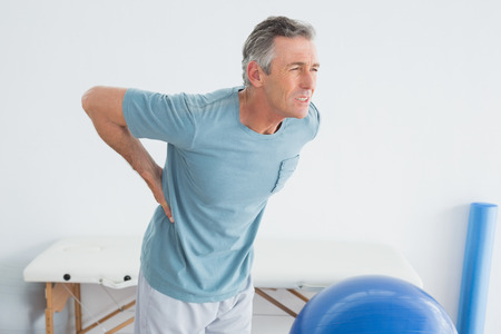 lower back pain: Mature man with lower back pain standing in the gym at hospital
