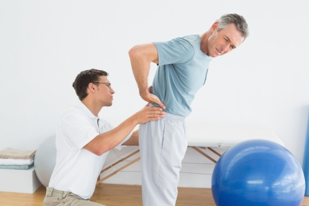 Side view of a male therapist massaging mans lower back in the gym at hospital Banco de Imagens
