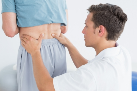 Close-up of hands massaging mans lower back in the gym at hospital photo