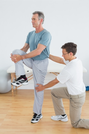 Side view of a male therapist helping man with stretching exercises in the gym at hospital