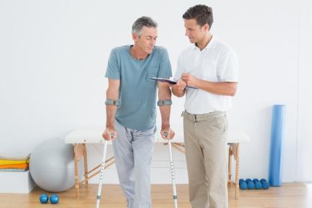 Mannelijke therapeut bespreken van rapporten met een gehandicapte patiënt in de sportschool in het ziekenhuis Stockfoto