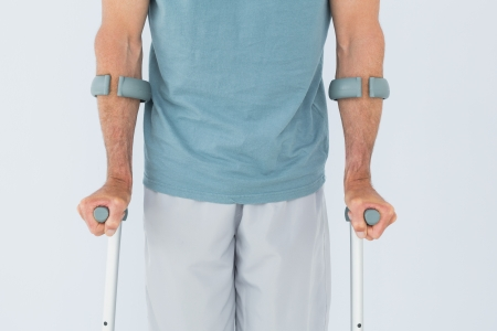 Close-up mid section of a man with crutches standing against white background