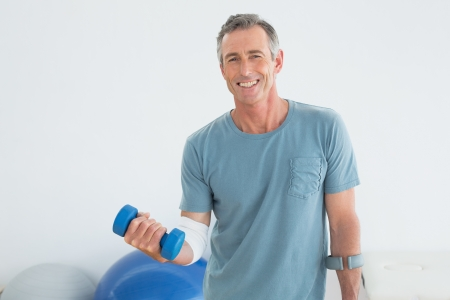 Portrait of a smiling mature man with crutch and dumbbells at the gym hospital photo