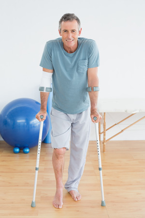 Full length portrait of a smiling mature man with crutches at the gym hospital