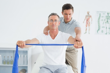 25503530: Male therapist massaging mans shoulder in the hospital