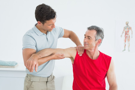Male physiotherapist massaging mature mans arm in the hospital