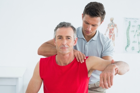 Male physiotherapist stretching a mature mans arm in the hospital