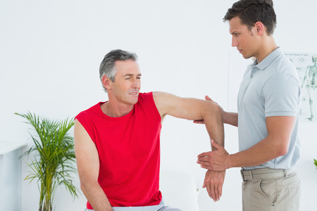 strength therapy: Male physiotherapist stretching a mature mans arm in the hospital