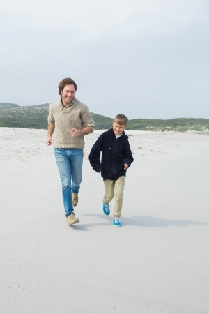 Full length of a young man and son jogging at the beach photo
