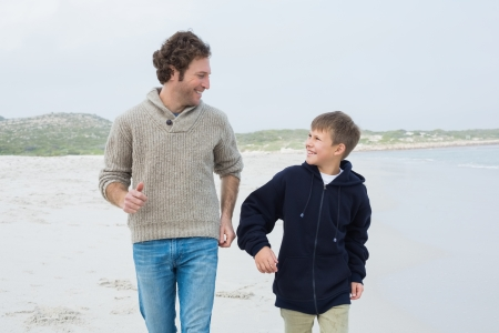 Happy young man and cheerful son jogging at the beach photo